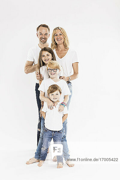 Happy family with children standing in row against white background