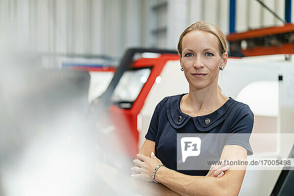Confident businesswoman with arms crossed standing against machinery in industry