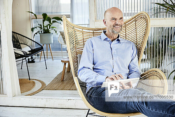 Smiling businessman using wireless computer keyboard while sitting on chair at home