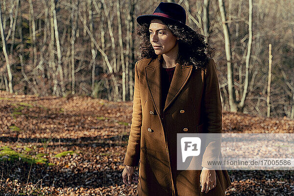 Woman wearing jacket and hat looking away while standing in forest