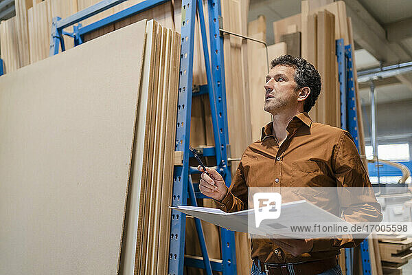 Portrait of carpenter standing with ring binder in front of shelves with wooden planks