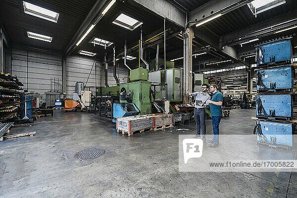Männliche Kollegen stehen in einer Produktionsstätte