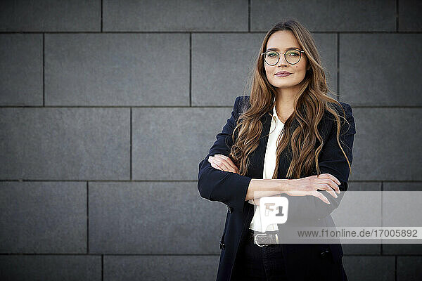 Confident female professional standing with arms crossed against brick wall