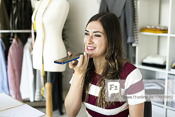 Smiling female design professional sending voicemail through smart phone while sitting at studio