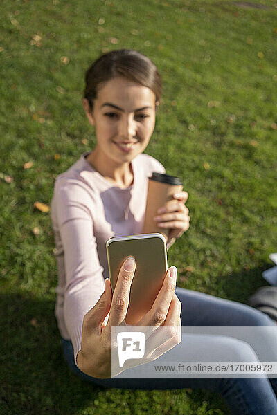 Young female entrepreneur taking selfie trough smart phone while sitting on grass in park during autumn