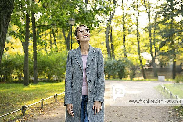 Lächelnde Geschäftsfrau  die beim Gehen im Park nach oben schaut Lächelnde Geschäftsfrau, die beim Gehen im Park nach oben schaut