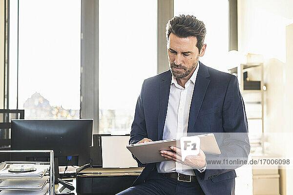 Geschäftsmann im Anzug  der ein digitales Tablet benutzt  während er im Büro sitzt Geschäftsmann im Anzug, der ein digitales Tablet benutzt, während er im Büro sitzt
