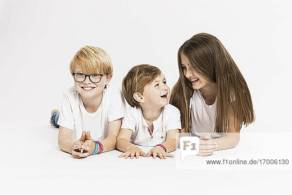 Cheerful siblings lying on front over white background