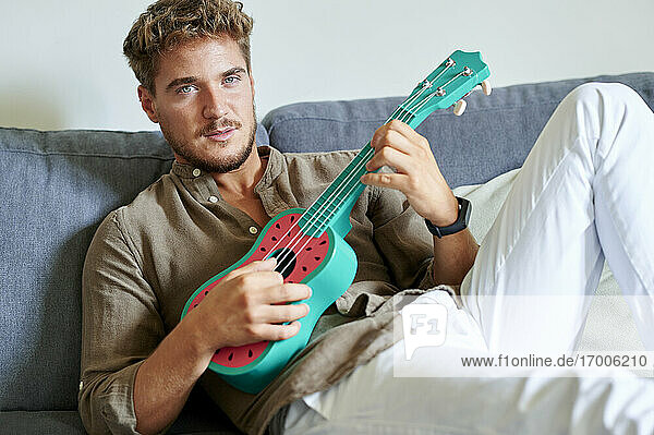 Young man learning ukulele while sitting on sofa in living room