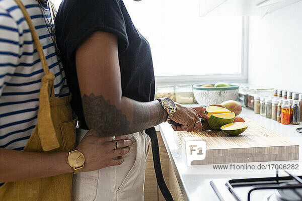 Young woman embracing girlfriend cutting mango fruit while standing in kitchen at home