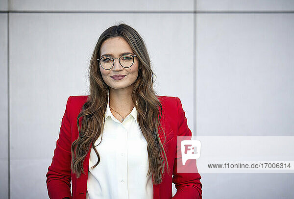 Smiling businesswoman wearing red blazer standing against wall