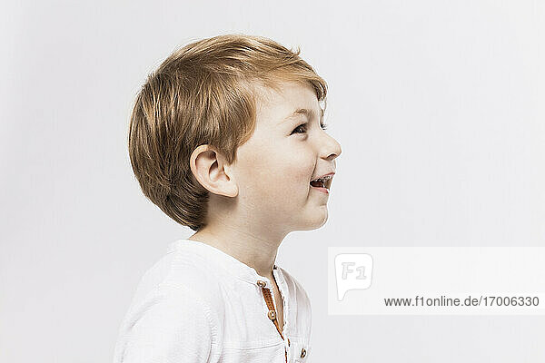 Happy cute boy looking away against white background