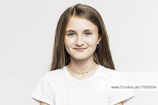 Smiling girl with brown hair against white background
