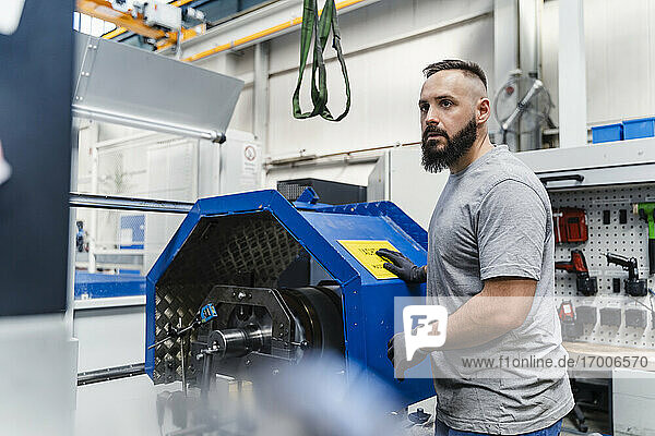 Nachdenklicher männlicher Techniker  der an einer Maschine in einer Fabrik steht und wegschaut