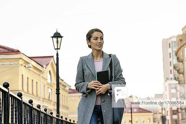 Unternehmerin  die im Herbst in der Stadt steht und wegschaut Unternehmerin, die im Herbst in der Stadt steht und wegschaut