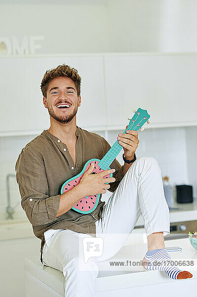 Cheerful young man playing ukulele while sitting on kitchen counter