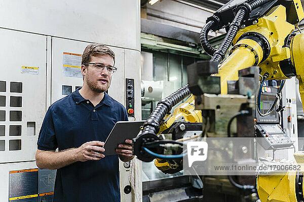 Männlicher Arbeiter hält ein digitales Tablet während einer Untersuchung in der Industrie