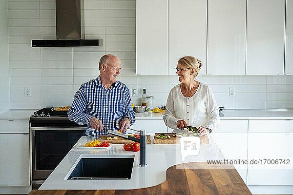 Älteres Paar unterhält sich beim Gemüseschneiden auf der Kücheninsel zu Hause