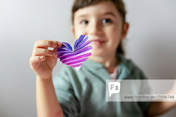 Happy girl holding handmade heart with origami against wall