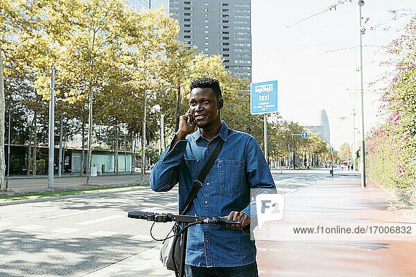 Männlicher Pendler  der mit einem elektrischen Roller auf dem Bürgersteig in der Stadt mit seinem Smartphone telefoniert Männlicher Pendler, der mit einem elektrischen Roller auf dem Bürgersteig in der Stadt mit seinem Smartphone telefoniert