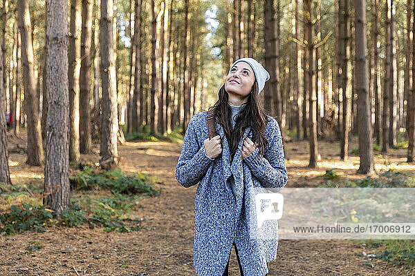 Smiling woman looking up while hiking in Cannock Chase forest during winter
