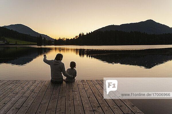 Mutter und kleine Tochter sitzen in der Abenddämmerung zusammen am Ende eines Stegs am Seeufer