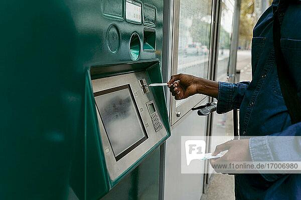 Geschäftsmann kauft ein Ticket  während er seine Kreditkarte in den Automaten steckt Geschäftsmann kauft ein Ticket, während er seine Kreditkarte in den Automaten steckt