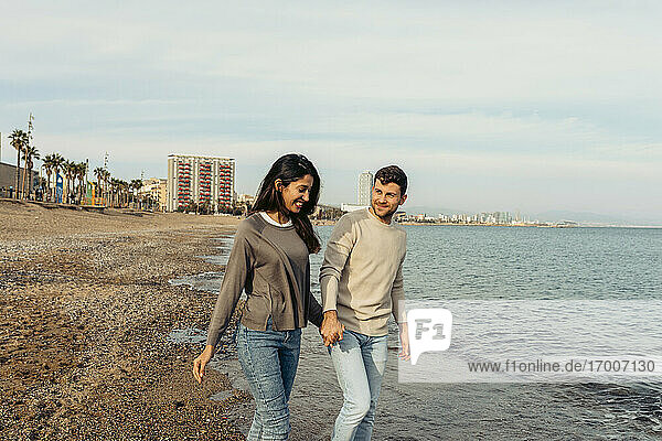 Smiling young woman holding man's hand while walking against sky at beach