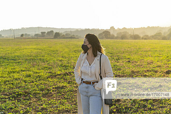 Young woman wearing protective face mask while enjoying countryside during pandemic