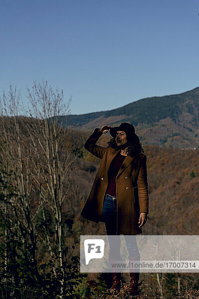 Woman wearing hat looking around while standing in forest