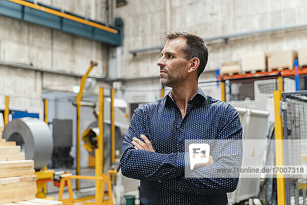 Thoughtful male entrepreneur with arms crossed looking away while standing in factory