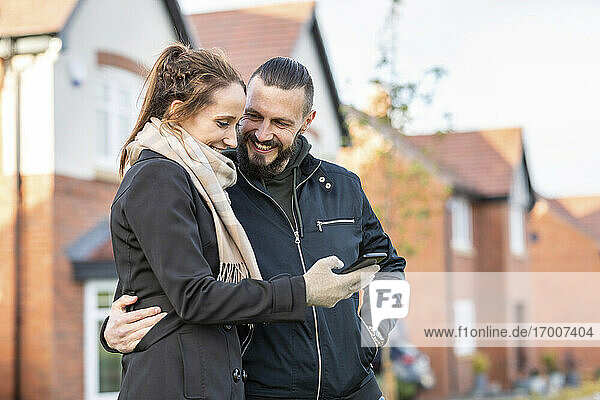 Smiling man looking at girlfriend using smart phone while standing against new houses