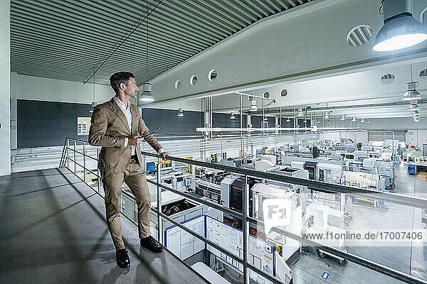 Geschäftsmann im Anzug mit Blick auf Maschinenausrüstung in der Industrie