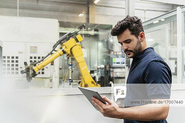 Männlicher Fabrikarbeiter  der im Stehen ein digitales Tablet in der Fertigungsindustrie benutzt