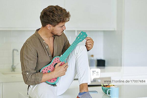 Junger Mann mit Ukulele über Küchentheke sitzend zu Hause Junger Mann mit Ukulele über Küchentheke sitzend zu Hause