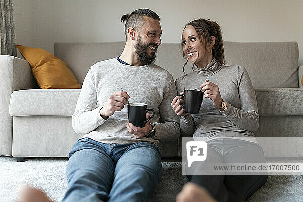 Smiling couple looking at each other while sitting on carpet in living room at home