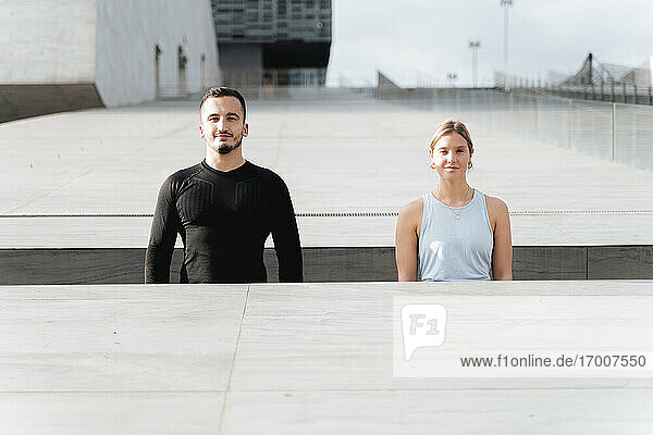 Couple in sports clothing standing by retaining wall