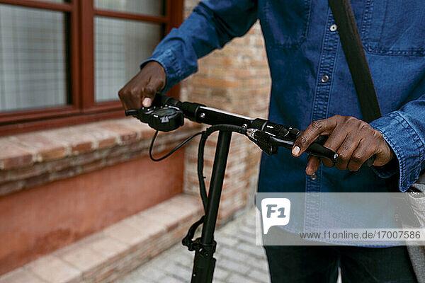 Männlicher Pendler mit Elektroroller auf dem Fußweg Männlicher Pendler mit Elektroroller auf dem Fußweg