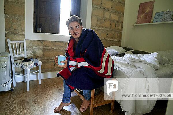 Nachdenklicher Mann mit Kaffeetasse  der wegschaut  während er auf einem Tisch im Schlafzimmer sitzt Nachdenklicher Mann mit Kaffeetasse, der wegschaut, während er auf einem Tisch im Schlafzimmer sitzt
