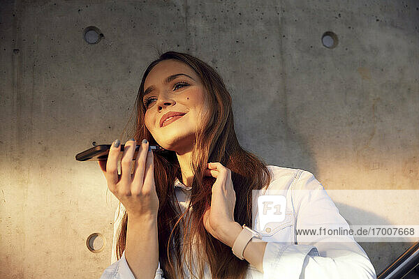 Smiling businesswoman hand in hair talking on mobile phone while standing against wall