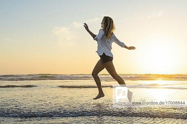 Unbekümmerte Frau  die bei Sonnenuntergang mit ausgestreckten Armen gegen das Meer läuft Unbekümmerte Frau, die bei Sonnenuntergang mit ausgestreckten Armen gegen das Meer läuft