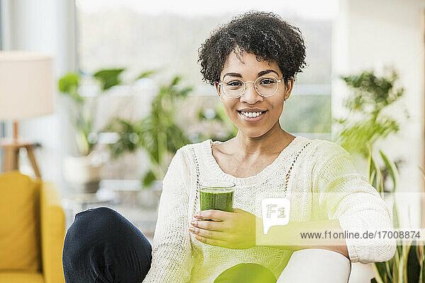 Junge Frau mit Brille lächelt  während sie mit einem Saft zu Hause sitzt Junge Frau mit Brille lächelt, während sie mit einem Saft zu Hause sitzt