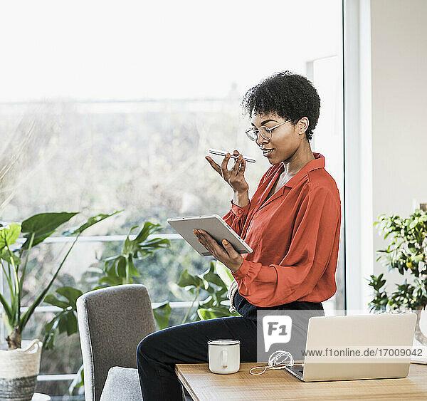Frau benutzt Smartphone und digitales Tablet am Tisch mit Laptop zu Hause Frau benutzt Smartphone und digitales Tablet am Tisch mit Laptop zu Hause