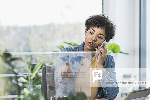 Woman talking on phone and using transparent display at home
