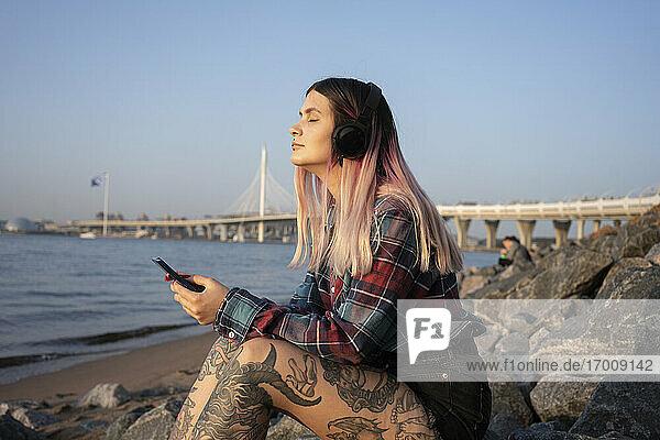 Modische Frau mit geschlossenen Augen hört Musik über Kopfhörer auf einem Felsen am Strand Modische Frau mit geschlossenen Augen hört Musik über Kopfhörer auf einem Felsen am Strand