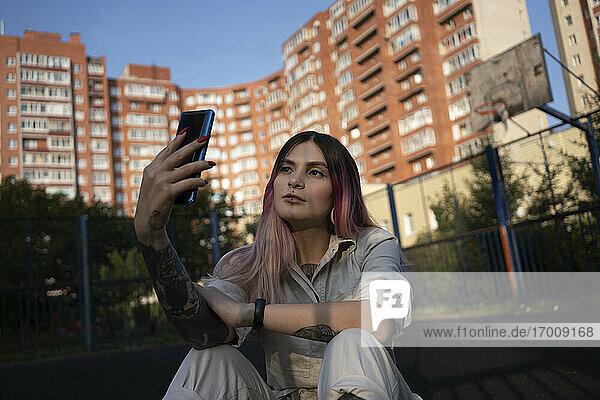 Junge Frau  die ein Selfie mit ihrem Mobiltelefon auf dem Sportplatz macht Junge Frau, die ein Selfie mit ihrem Mobiltelefon auf dem Sportplatz macht