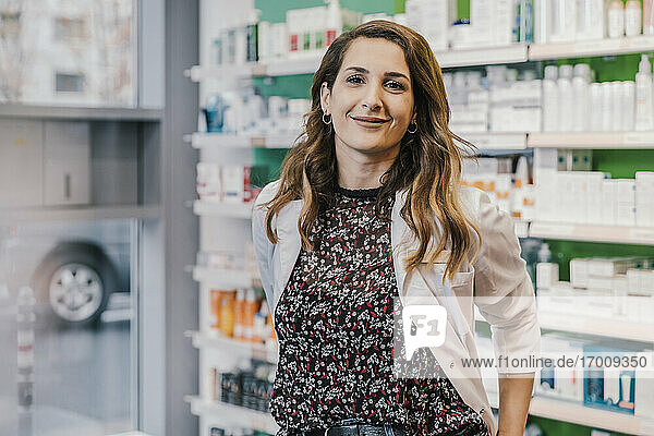 Confident pharmacist wearing lab coat in chemist shop