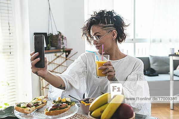 Porträt einer jungen Frau  die ein Selfie mit ihrem Smartphone macht  während sie frühstückt