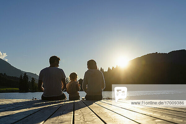 Family with little daughter sitting together at end of lakeshore jetty at sunset