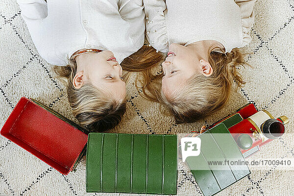 Sisters looking at each other while lying by toy train on carpet